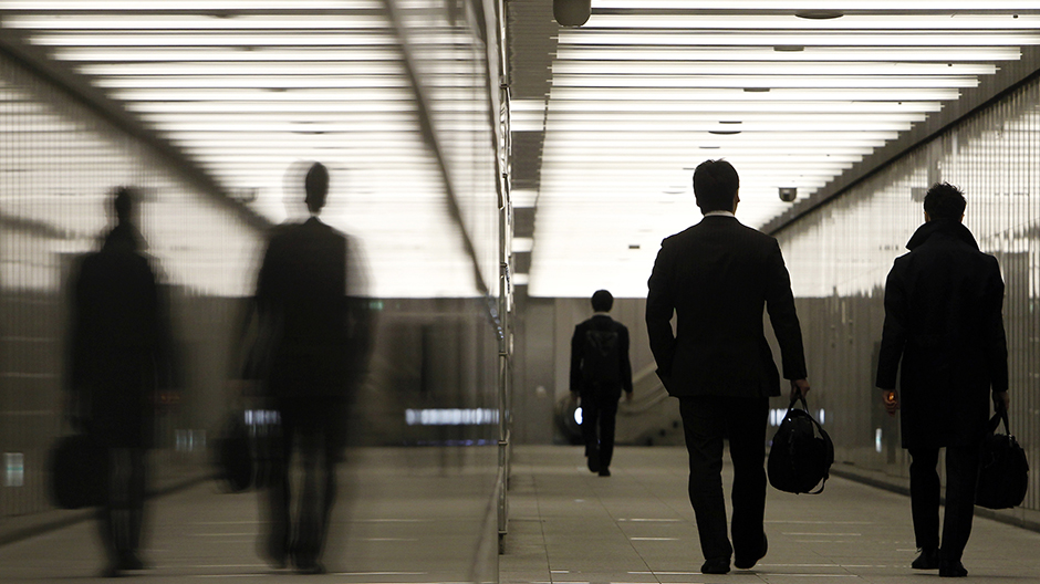 Businessmen walk through a business complex in Tokyo January 11, 2011
